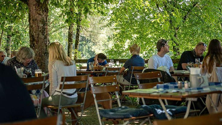 Ein halb voller Biergarten. Blätterdach, Menschen an Tischen, Klappstühle, Gespräche.