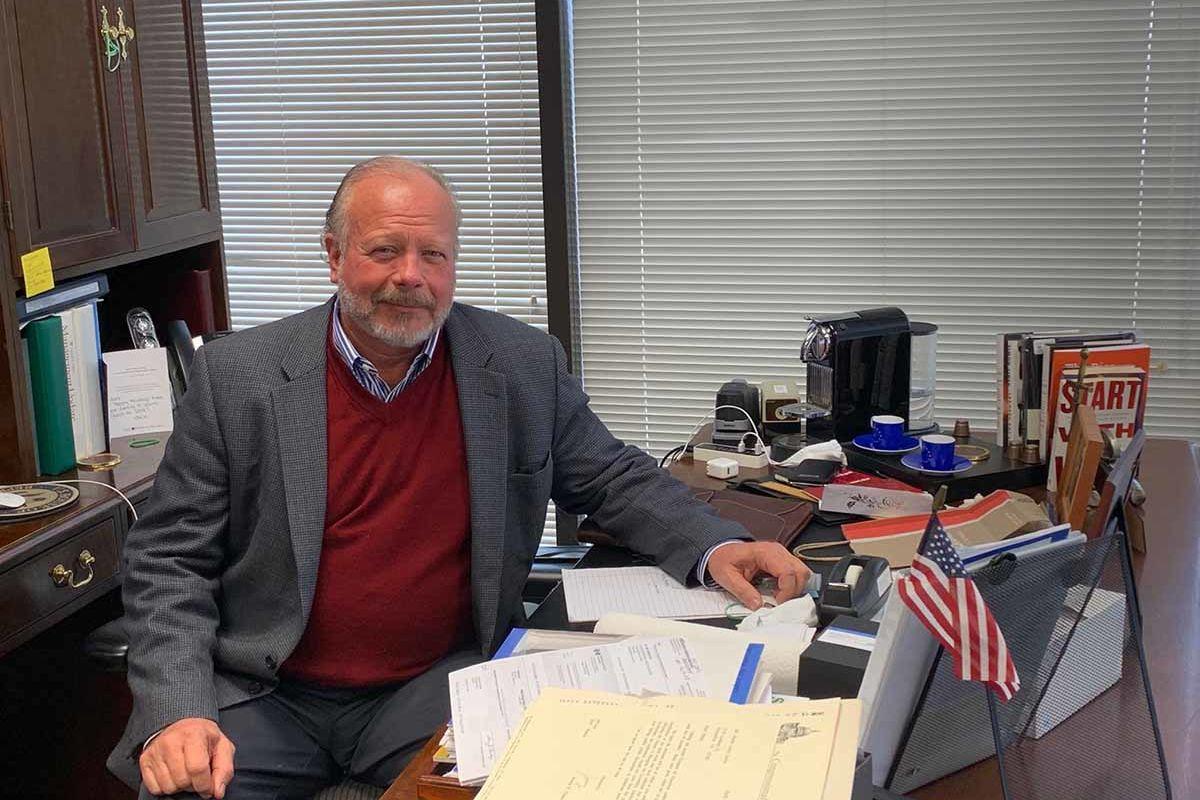 Mark Strand, ein älterer Herr mit freundlichem, rundem Gesicht, Tweedsacko und Pullover sitzt an einem übervollen Schreibtisch, an dem er sich sichtlich wohl zu fühlen scheint und lächelt in die Kamera.