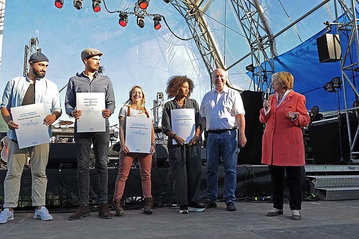 Die drei Preisträger zusammen mit Männle und Niedermeier auf der Bühne, die Preisurkunden vor sich haltend.
