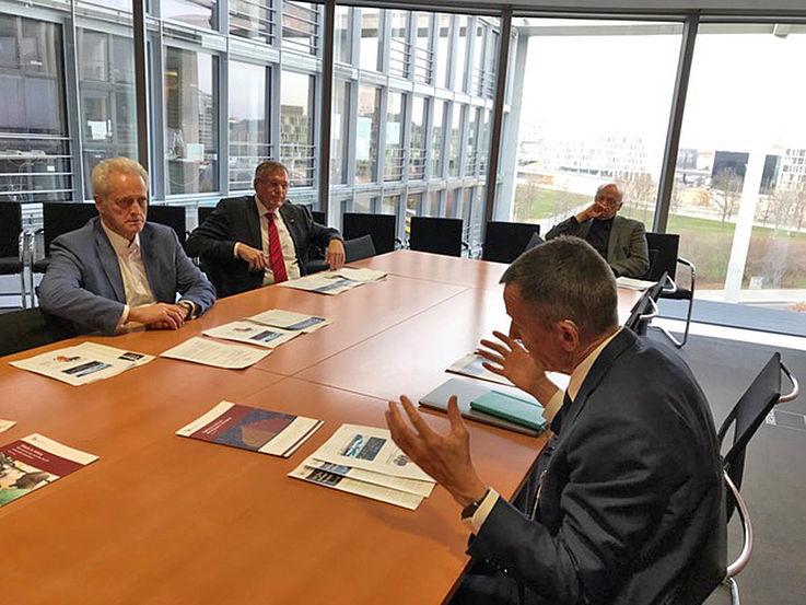 Konferenztisch mit vier Männern. Vorne im Bild unterstreicht der Sprecher seine Worte mit seinen Händen, als hielte er ein Scheit Holz.