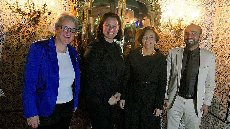 Vier Personen, abends lachend vor einer orientalisch verzierten Wand und goldener Vitrine.