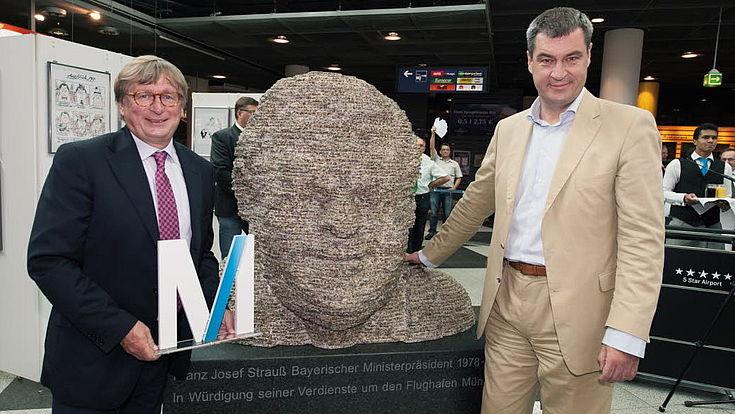 """Dr. Michael Kerkloh, Vorsitzender der FMG-Geschäftsführung, und Heimatminister Markus Söder neben der Skulptur """"FJS – ein bayerisches Urgestein"""" von Hubert Maier"""