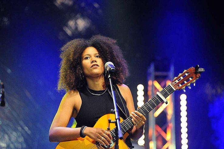Junge Frau mit Gitarre, singend.