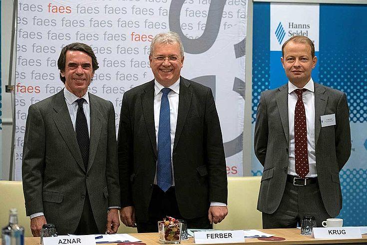 Drei Herren im Anzug stehen hinter ihren Plätzen am Konferenztisch und lächeln.