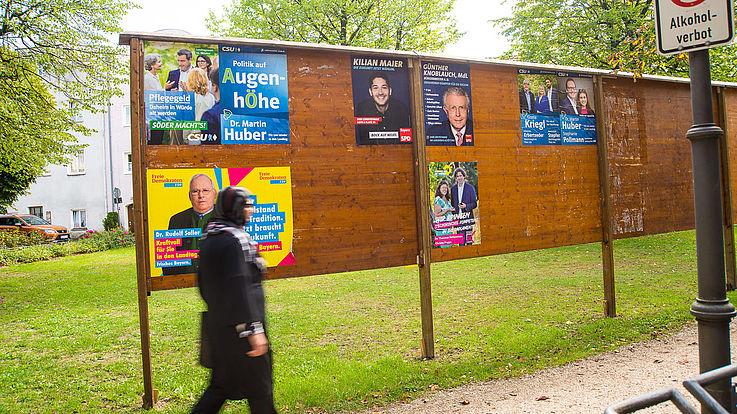 Frau geht an Wahlplakaten vorbei.