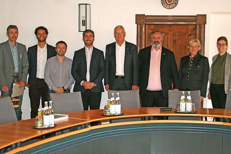 Gruppenbild mit acht Menschen hinter einem Runden Konferenztisch.