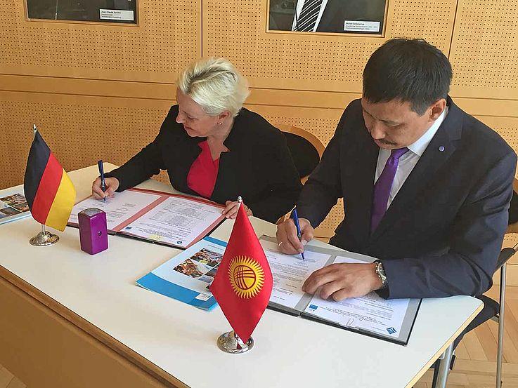 Frau Luther und der Delegationsleiter unterzeichnen ein Dokument vor kleinen Fähnchen ihrer Länder.