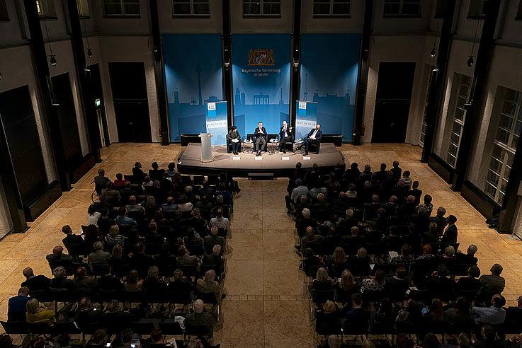 Eine große langer Saal mit Säulen am Rande und einem Podium ganz vorne, auf dem sich Menschen unterhalten. Voll besetzte Stuhlreihen.