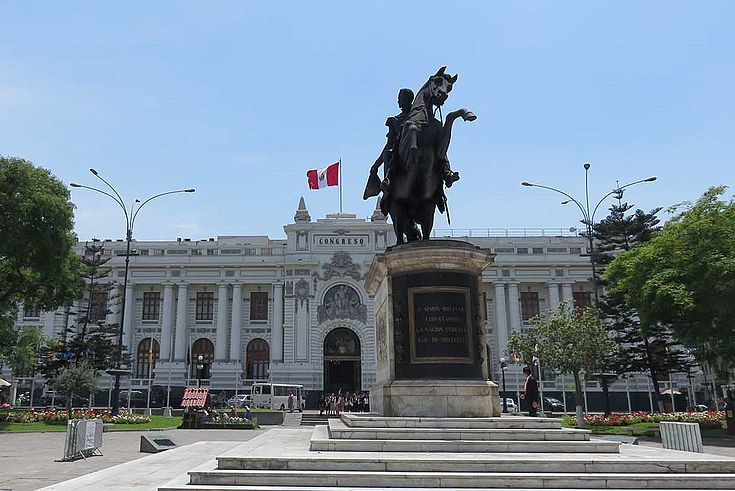 Das weiße Kongress-Gebäudes des peruanischen Parlamentes wird von Bäumen umrahmt. Davor steht ein Reiterdenkmal.
