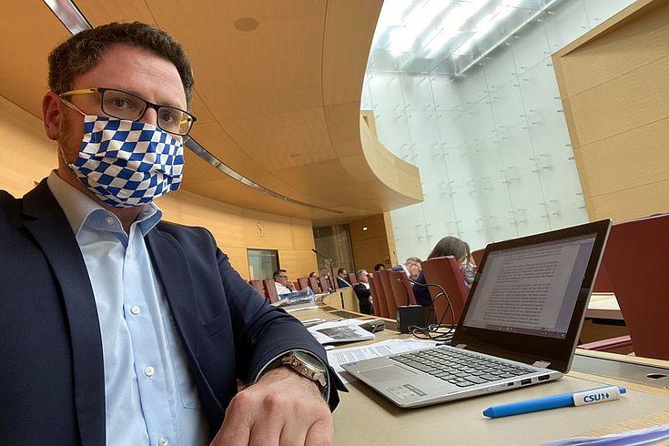 Hopp im Anzug allerdings ohne Krawatte aber mit Mund-Nasenschutz auf seinem Platz im Bayerischen Landesparlament