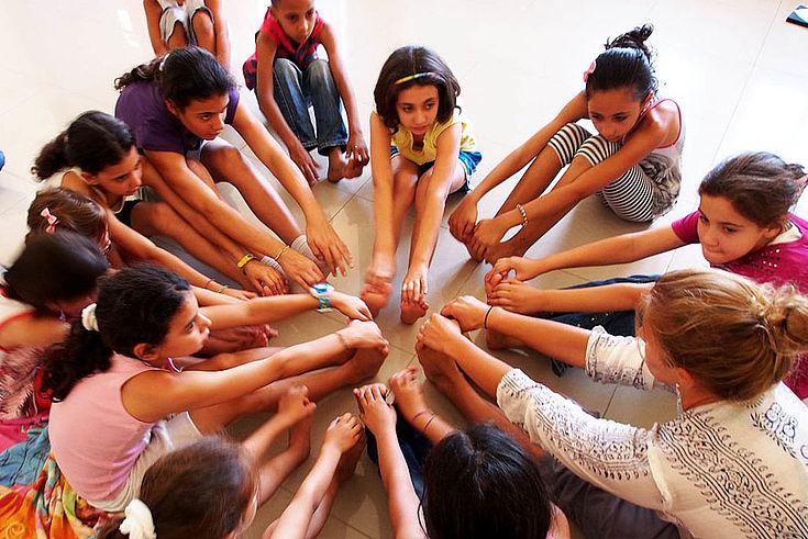 """Eine Gruppe Kinder sitzen im Kreis, die Hände in die Mitte gestreckt und lachen fröhlich. Symbol für """"Gemeinsam"""""""