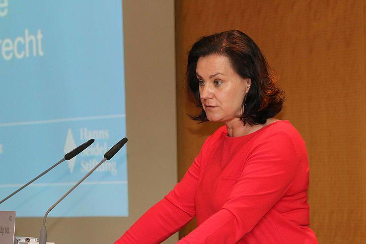 Frau mit entschlossenem Gesicht am Rednerpult von der Seite aufgenommen. Die Hände forsch aufgestützt.