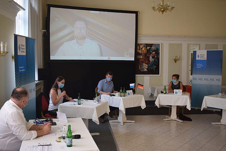Besprechungsraum mit Konferenztischen in einem Kreis. Bildschirm im Hintergrund, auf dem ein Mann zu sehen ist, der wohl mitspricht.