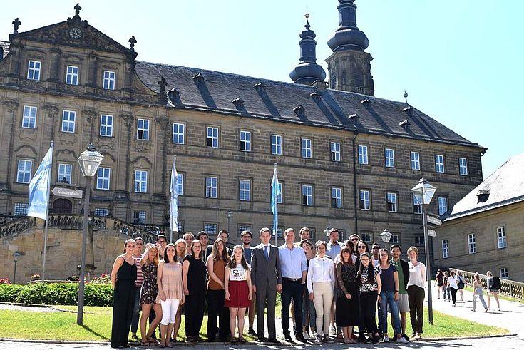 In der Mitte: Staatssekretär Thomas Silberhorn (l.) und der Leiter des HSS-Hauptstadtbüros, Dr. Alexander Wolf (r.) mit den Parlamentsstipendiaten vor Kloster Banz