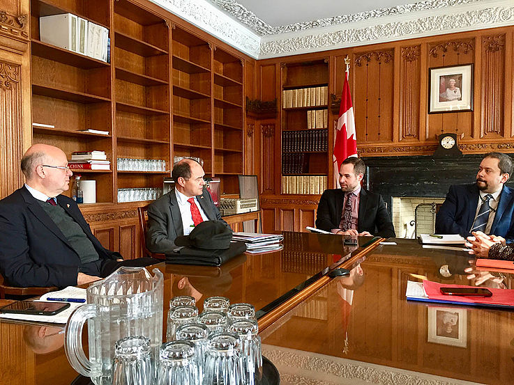 Holzgetäfelter Raum mit edlem Konferenztisch. Alles sehr edel. Darum vier Männer im Gespräch