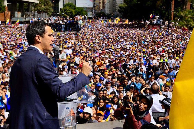 Guaidó hält eine Ansprache vor einer riesigen Menschenmenge in Caracas. Ballt die Faust. Entschlossen.