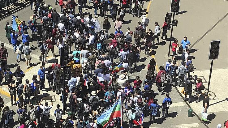 Eine Menge von Menschen mit Fahnen ziehen auf einen Platz