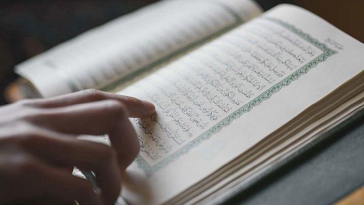 Ein Finger fährt über eine Sure im Koran.