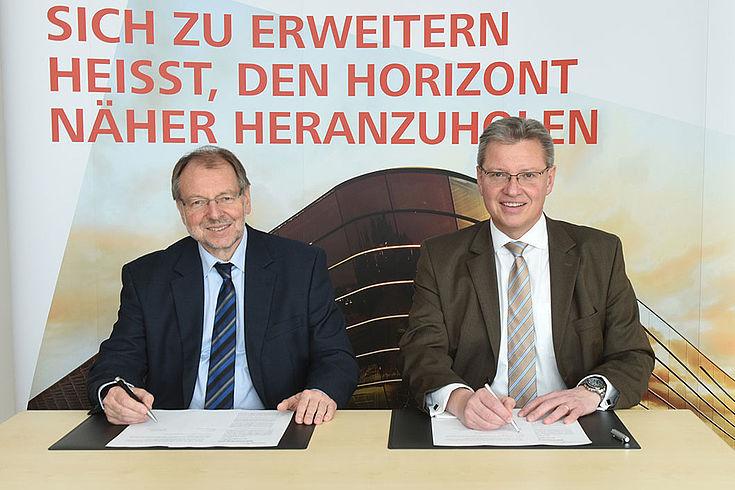 """nwand, auf der stehDr. Peter Witterauf (HSS) und Dr. Roland Fleck sitzen lächelnd vor Unterschriftenmappen vor einer Leit: """"Sich zu erweitern heißt, den Horizont heranzuholen"""""""