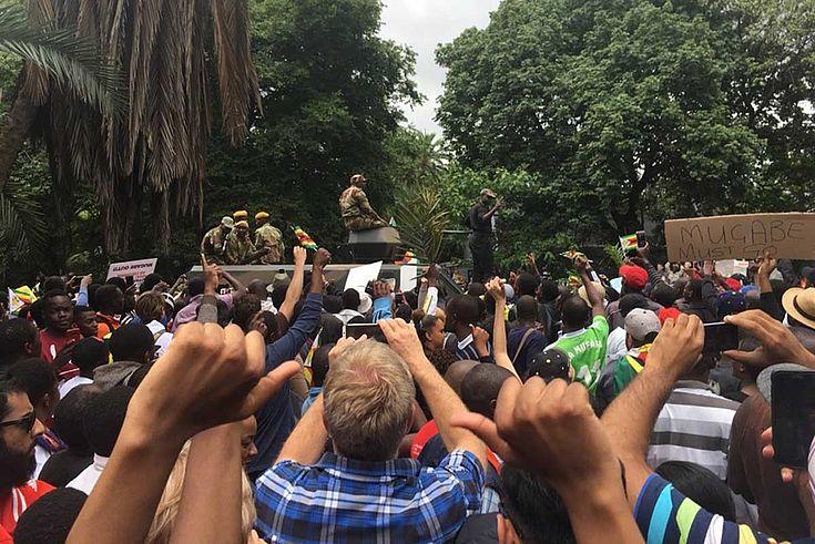 Tumult in der demonstrierenden Menge. Im Hintergrund Armeefahrzeuge.