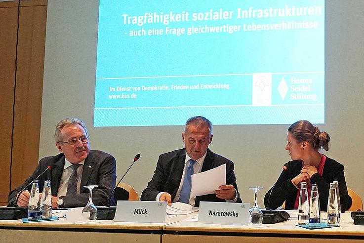 Drei Personen auf dem Podium. Der Herr in der Mitte blättert in Unterlagen.