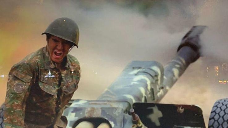 Ein Soldat feuert jubelnd eine Haubitze ab.