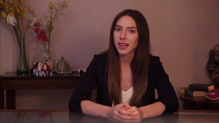 Junge Frau mit langen Haaren und dezent gekleidet spricht mit ernstem Gesicht, auf einem Stuhl sitzend in die Kamera.