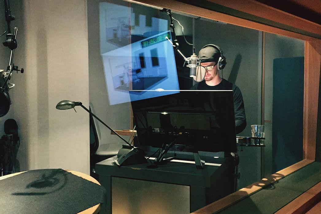 Hinter einer Glasscheibe sieht man ein Tonstudie in dem ein junger Mann mit Kopfhörern in ein großes Mikro spricht.