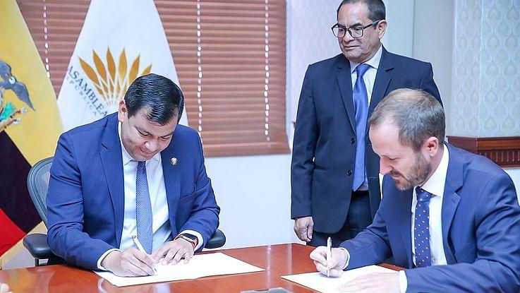 Zwei Herren sitzen an einem Tisch und unterzeichnen ein Abkommen. Rechts im Hintergrund steht ein weiterer Herr und beobachtet das Geschehen