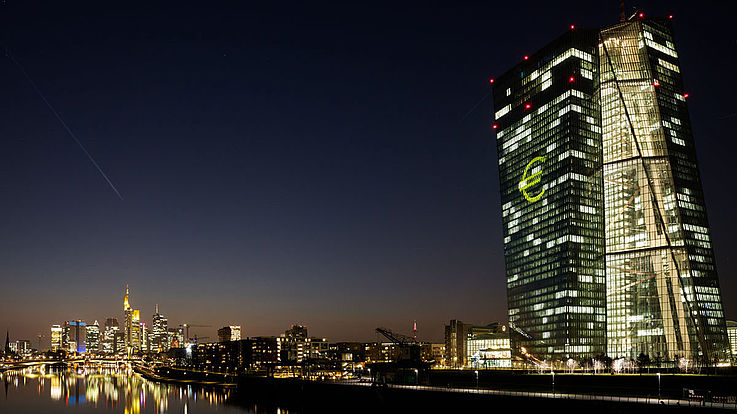 Das erleuchtete EZB-Gebäude am Fluss in Frankfurt. Ein großes Eurozeichen an der Glasfassade.