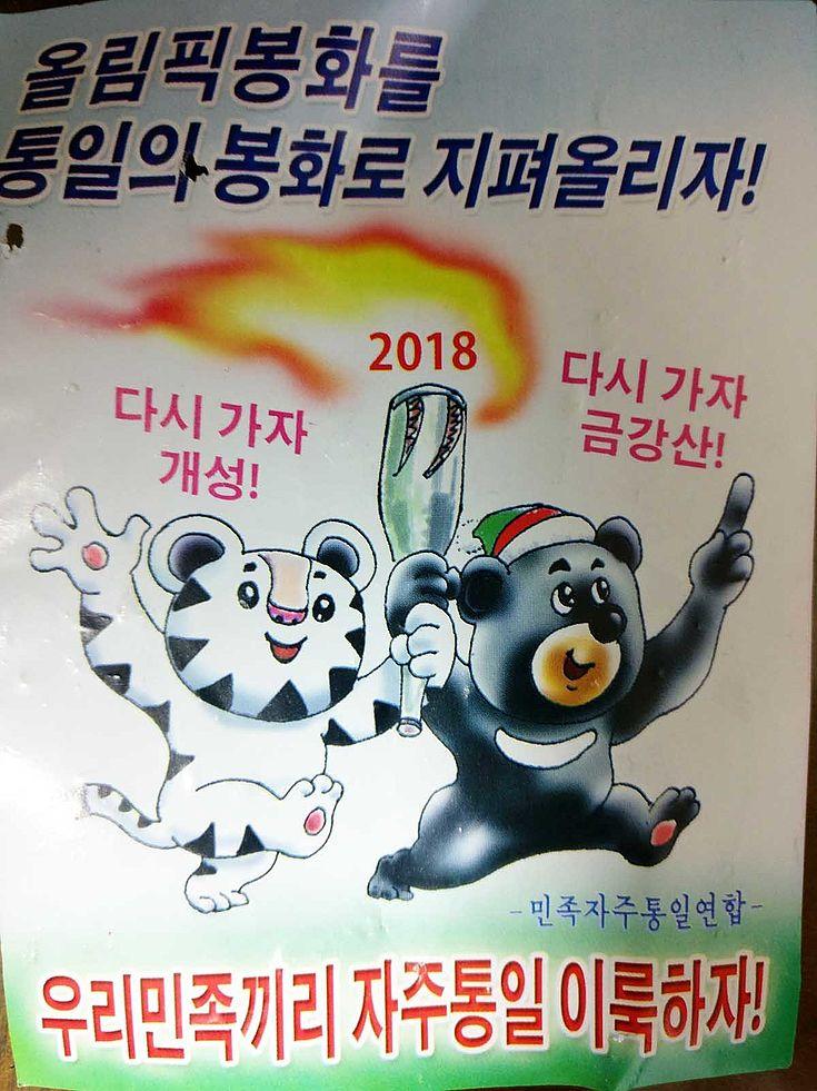 Bär und Tiger halten gemeinsam die olympische Fackel und laufen lachend nach rechts aus dem Bild