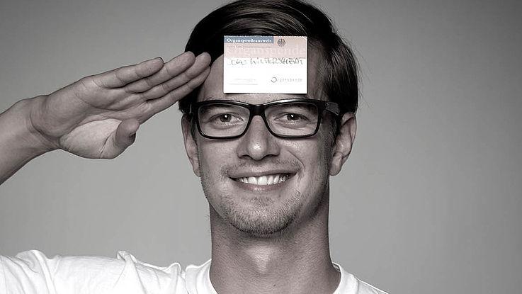 Junger Mann mit weißen T-Shirt und Hornbrille grüßt mit rechter Hand am Kopf und lächelt.
