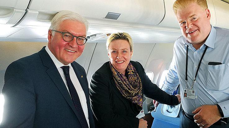 Der Bundespräsident im Innenraum eines Flugzeugs. Er lächelt zuasmmen mit Dr. Luther und Herrn Niemann in die Kamera.