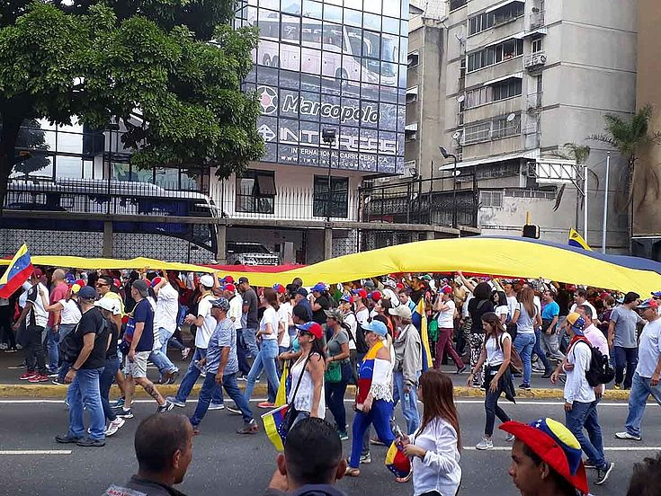 Menschenmenge mit Flaggen zieht durch eine breite Straße.