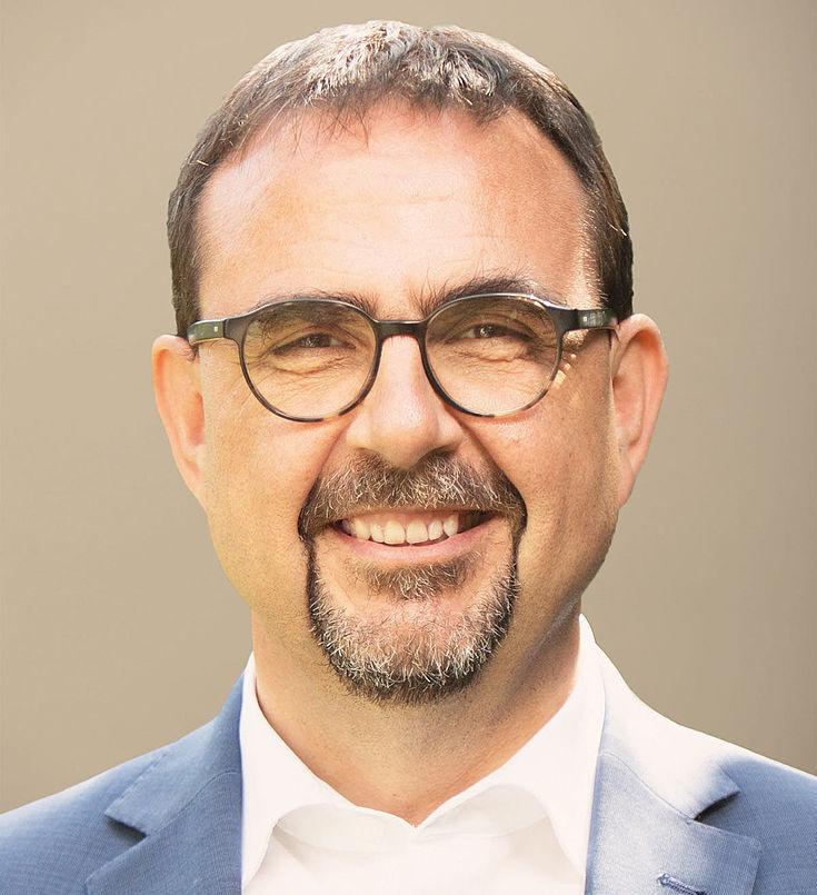 Ein freundlich lächelnder Mann mit Brille und Kinnbart