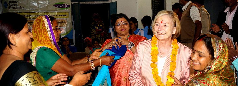 Ursula Männle (Mitte) beim Dorfparlament in Jaipur. Prof. Männle mit Blumenkette und indischer Kleidung wird von einer Gruppe indischer Frauen in Saris empfangen.