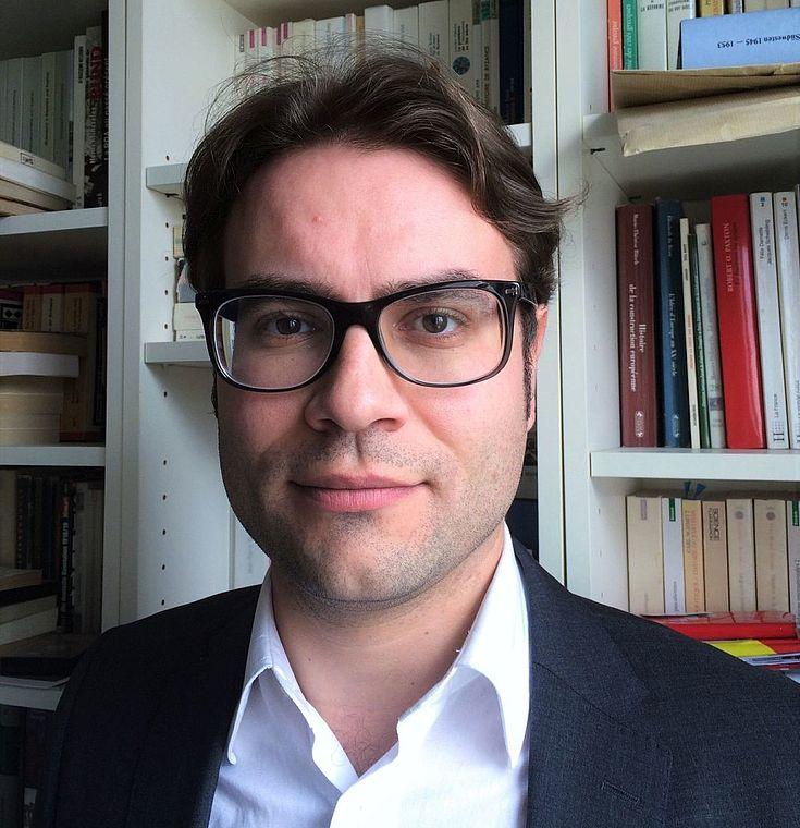 Gemessen blickender Mann ohne Krawatte vor einem Bücherregal