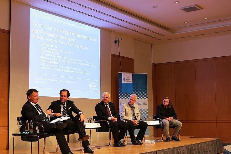 Fünf Männer auf dem Podium diskutierend