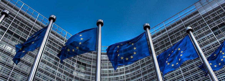 Vier Flaggen mit den Europasternen vor dem Kommissionsgebäude in Brüssel. Oben der Himmel.