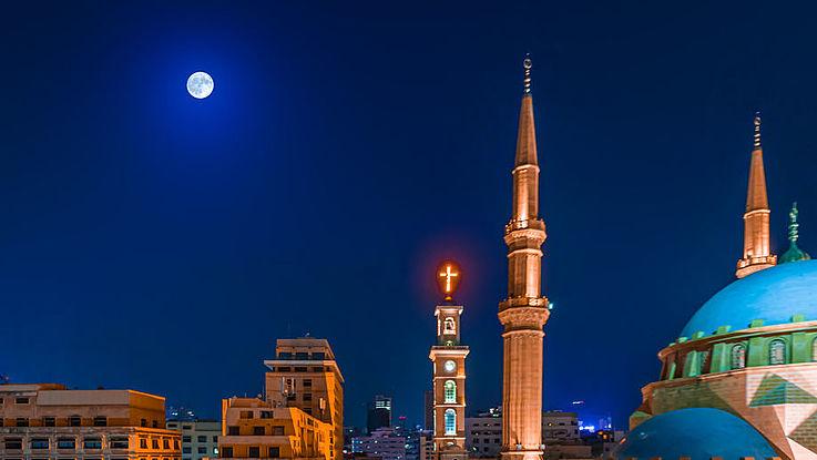 Eine Straße in Beirut in der Nacht. Vorne eine Moschee, hinten das Kreuz einer christlichen Kirche.