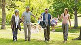 Vater, Mutter, Kind und Großeltern haten sich an den Händen und spazieren durch den Park