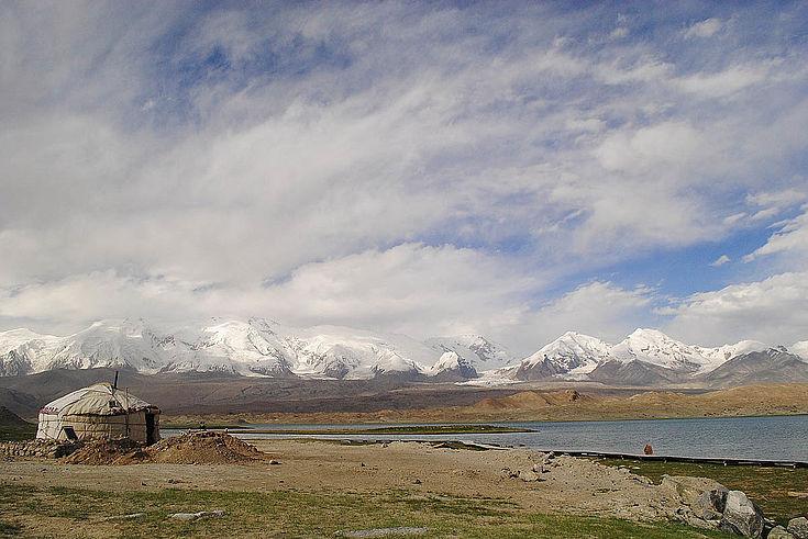 Eine Jurte am linken Bildrand an einem weiten Hochgebirgssee. Schneebedeckte Gipfel bevölkern den Horizont, die Ausläufer des Himalaja.
