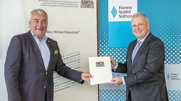Spenle und Ferber halten zusammen einen Vertrag hoch und lächeln, im Hintergund sind die Logos der Institutionen zu sehen