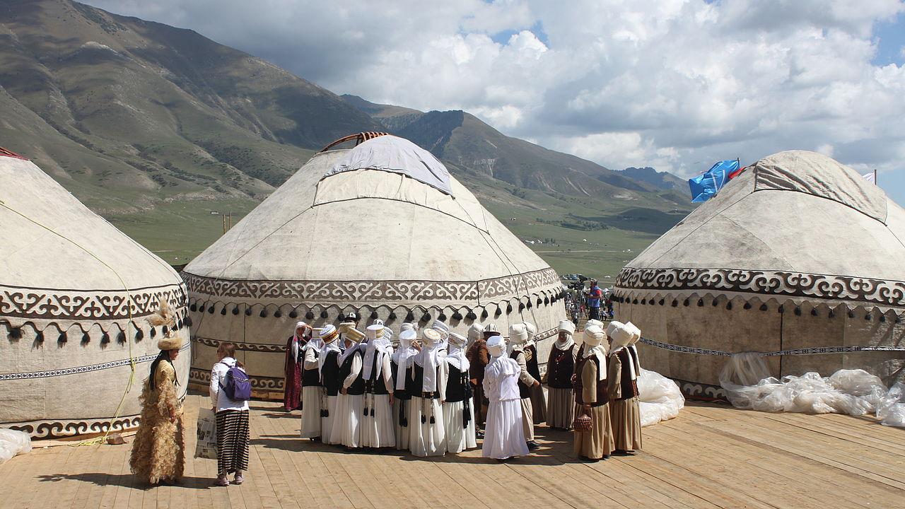 Drei helle Jurten und davor eine gruppe traditionell gekleideter Nomaden