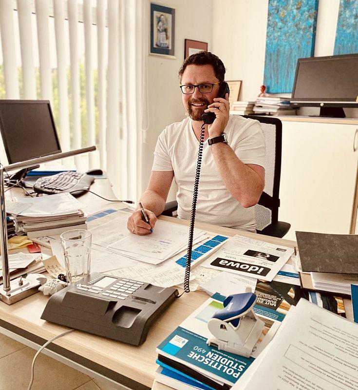 Ein telefonierender Mann an seinem überfüllten Schreibtisch. Geschäftige Atmosphäre.