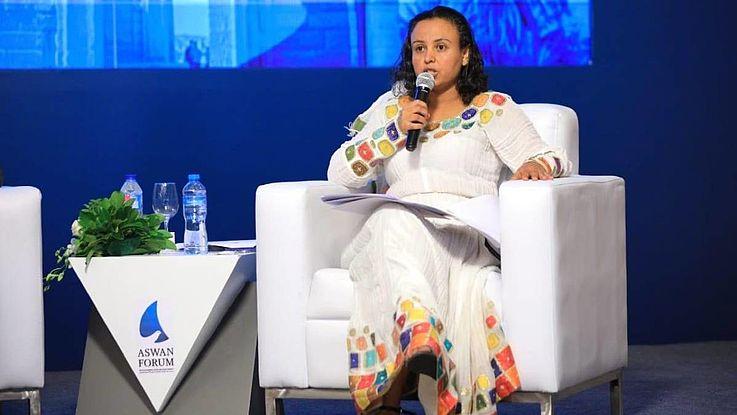 Abebe, eine junge Frau mit fröhlichem Kleid afrikanischen Stils, sitzt selbstbewusst auf einem Podium und spricht in ein Mikro.