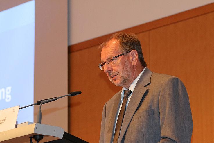 Am HSS-Rednerpult, von unten aufgenommen, schütteres Haar, randlose Brille, grauer Anzug, grauer Vollbart, ernster Gesichtsausdruck