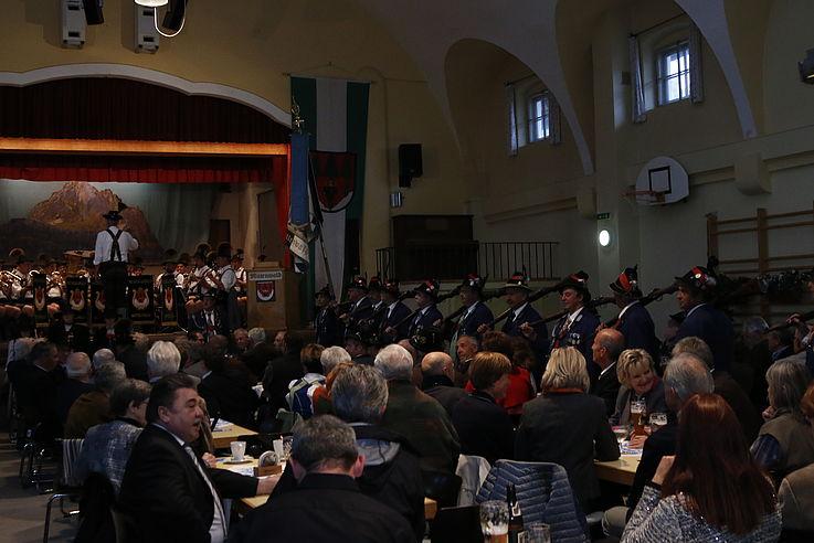 Rechts eine Gruppe von Männern mit Gewähren, vorne auf der Bühne die Musikkapelle