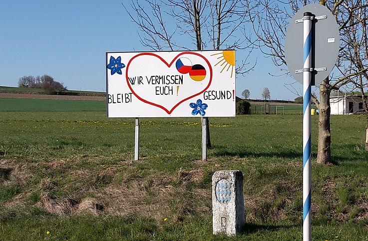Schild, auf dem in einem kindlich gemalten Herzen zu lesen ist: Wir vermissen euch