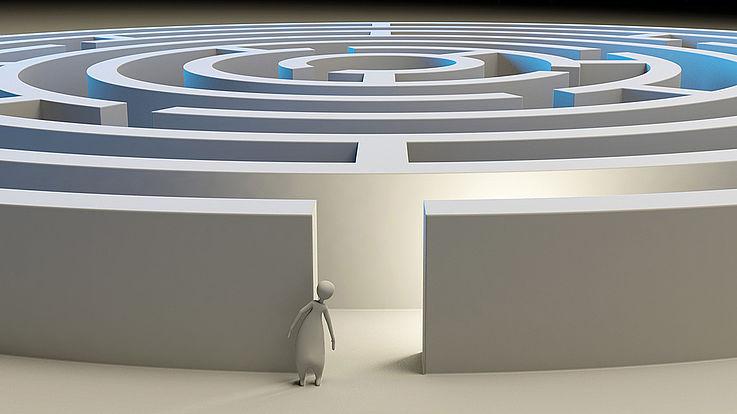 Stilisiertes Strichmännchen steht vor dem Eingang zu einem Labyrinth